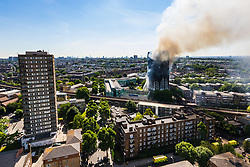 London, June 14th 2017. A fire rages through a residential tower block, Grenfell Tower, in Kensington, West London, with the entire building engulfed in flames. More than 200 firefighters are attending the incident and there are reports of people trapped inside. No figures are available as to casualties. PICTURED: The fire viewed from a nearby tower block.