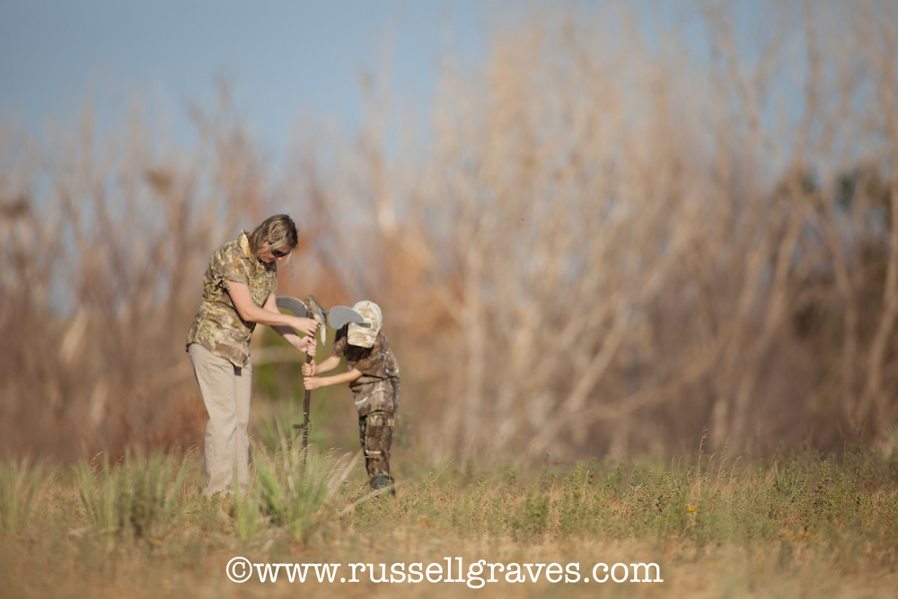 MOTHER AND SON DOVE HUNTERS WEARING REALTREE CAMOUFLAGE AND SETTING OUT A MOJO DOVE DECOY
