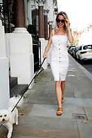 Leila Russack (aka singer songwriter Miss Zagato) walking her dog in Kensington wearing a  white denim dress by Mother.