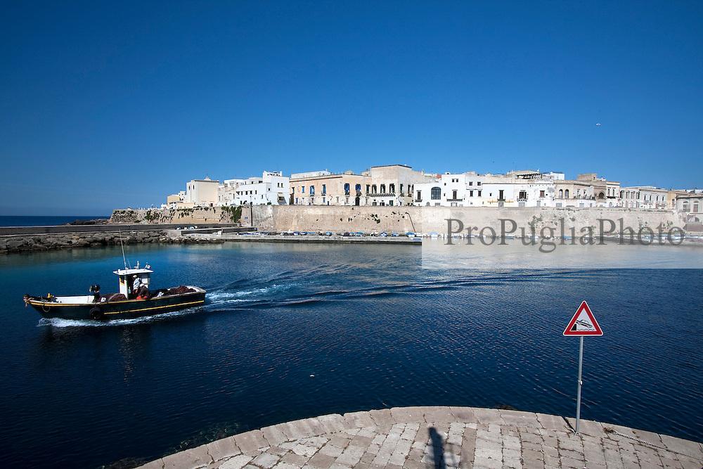 Barca da pesca lascia il porto di Gallipoli (LE). Sullo sfondo una porzione della città vecchia.