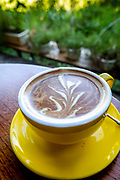 cappuccino served in a yellow cup and saucer. RAW to Jpg