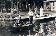 "President Calvin Coolidge (right) fishes the Brule River in Douglas County, Wisconsin, with Native American guide John LaRock in 1928. The canoe is named ""Beaver Dick"" and in the back is Coolidge's white collie, Rob Roy."