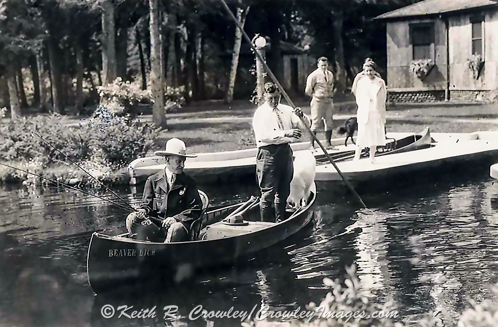 """President Calvin Coolidge (right) fishes the Brule River in Douglas County, Wisconsin, with Native American guide John LaRock in 1928. The canoe is named """"Beaver Dick"""" and in the back is Coolidge's white collie, Rob Roy."""