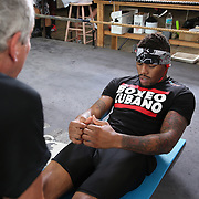 """WINTER HAVEN, FL - MAY 05: Boxer Willie Monroe Jr. does sit-ups  with Danny Akers at the Winter Haven Boxing Gym on May 5, 2015 in Winter Haven, Florida. Monroe will challenge middleweight world champion Gennady """"GGG"""" Golovkin for the WBA world championship title in Los Angeles on May 16.  (Photo by Alex Menendez/Getty Images) *** Local Caption *** Willie Monroe Jr.; Danny Akers"""