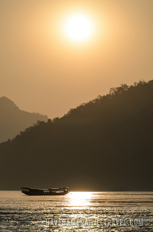 A wooden boat with a group of tourists is silhouetted against the setting sun on the Mekong River near Luang Prabang, Laos.