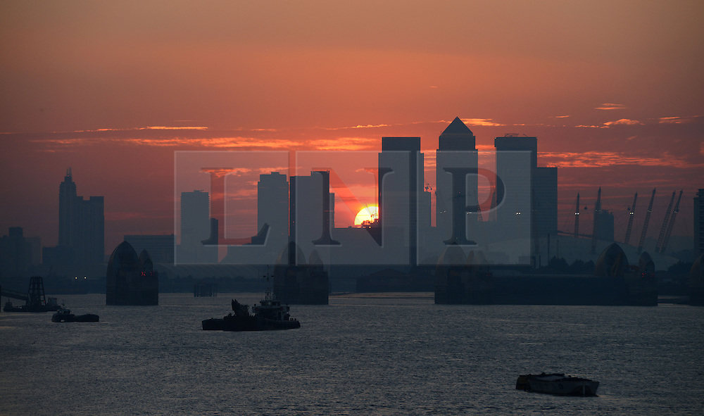 © Licensed to London News Pictures. 04/09/2013. London, UK. The Sun sets in a view from Woolwich, SE London in a picture showing The Thames Barrier, The O2 Arena, Canary Wharf. Photo credit: Mike KIng/LNP