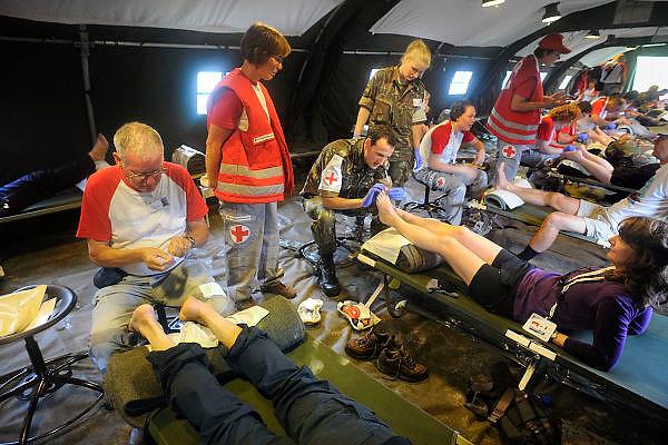 Nederland, Groesbeek, 23-7-2009Deelnemers aan de 4daagse, vierdaagse,  lopen op de derde dag, de dag van Groesbeek, o.a over de zevenheuvelenweg via de dijk bij Mook. Het is de zwaarste dag vanwege de heuvels en dit jaar bepaalde de regen het beeld. Ook was er de melding van een eerste geval van mexicaanse griep. In een legertent prikken vrijwilligers van het rode kruis blaren.The International Four Day Marches Nijmegen (or Vierdaagse) is the largest marching event in the world. It is organized every year in Nijmegen mid-July as a means of promoting sport and exercise. Participants walk 30, 40 or 50 kilometers daily, and on completion, receive a royally approved medal (Vierdaagsekruis). The participants are mostly civilians, but there are also a few thousand military participants. In 2004 a restriction on the maximum number of registrations is set for the first time. The maximum number of 47,000 registrations then has been reached within 6 weeks. More than a hundred countries have been represented in the Marches over the years. Today a case of mexican flu, swine flu, was reported.Foto: Flip Franssen/Hollandse Hoogte