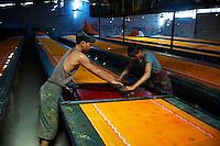 Inde, Rajasthan, Usine de Sari, impression des tissus. Les tissus sechent en plein air. Ramassage des tissus secs par des femmes et des enfants avant le repassage. Les tissus pendent sur des barres de bambou. Les rouleaux de tissus mesurent environ 800 m de long. // India, Rajasthan, Sari Factory, printing of the textile. Textile are dried in the open air. Collecting of dry textile  are folded by women and children. The textiles are hung to dry on bamboo rods. The long bands of textiles are about 800 metre in length.