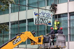 Specialist police officers use a cherry picker to approach two climate activists from HS2 Rebellion who scaled the Tower Place West building in the City of London in protest against the involvement of insurance company Marsh in the HS2 high-speed rail project on 2nd September 2021 in London, United Kingdom. Marsh insure subcontractors working on HS2.