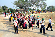Pa-O men dancing in the procession during a Shinbyu Novice Ceremony on 21st March 2016 in Mo Bye village, Shan State, Myanmar. In Myanmar, it is customary for boys to enter the monastery as a Buddhist novice between the age of ten and 20 years old although they can be as young as four, for at least one week. During the ceremony, which lasts two or sometimes three days, the boys dressed as princes are led on horseback through the village. Joining the procession are the boys' families, the parents carrying the monastic robes for the novices and the sisters or young village girls carrying flowers and ceremonial boxes.