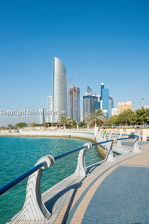 View along waterfront of Corniche towards modern office towers in Abu Dhabi United Arab Emirates