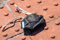 Barnsley Town Centre a lost or discarded face mask lies in the street, half way through the UK's third week of emergency measures which were announced Monday the 23rd April <br />
