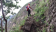 LIANGSHAN, CHINA - MAY 14: (CHINA OUT) <br /> <br /> Pupils from Atuler village climb vines hung on the cliff to go home after school on May 14, 2016 in Liangshan Yi Autonomous Prefecture, Sichuan Province of China. 72 families lived in Atuler village on the 800-meter cliff at Meigu River Canyon in Liangshan Yi Autonomous Prefecture. 15 pupils, aged 6 to 15, accompanied by 3 adults regularly spent 2 hours climbing 17 vines ladders hung on the 800-meter-high cliff to go between school and home twice a month. Villagers used the same ladders to go to the nearest market once a week to sell peppers and walnuts and buy necessities. <br /> ©Exclusivepix Media