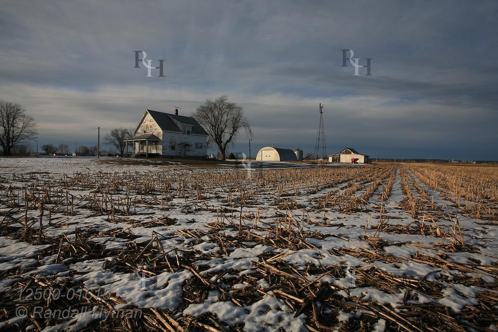 Snow melts into cornfields around dilapidated farmhouse near West Alton, Missouri.
