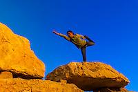 Woman doing a yoga pose atop a rock sculpture in the sculpture garden, Mitze Ramon, Negev Desert, Israel.