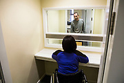 A prisoner arrives into a closed visit cell to talk to his wife. Closed visits take place in locked rooms with a toughened glass window between the prisoner and his visitor.  HMP/YOI Portland, Dorset. A resettlement prison with a capacity for 530 prisoners. Portland, Dorset, United Kingdom.