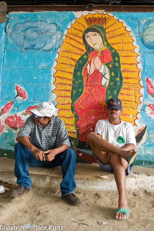 06 OCTOBER 2003 -- TAPACHULA, CHIAPAS, MEXICO:  Raft operators (balseros) in Hidalgo, Mexico, near Tapachula, on the Rio Suchiate, wait for customers under a mural of the Virgin of Guadalupe. Tapachula is center of the smuggling industry between Mexico and Guatemala. Consumer goods are smuggled south to Guatemala (to avoid paying Guatemalan import duties) and people are smuggled north into Mexico. Most of the people coming north are hoping to eventually get to the United States.  PHOTO BY JACK KURTZ