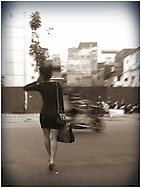 A stylish young woman crosses the street in Hanoi, Vietnam, Southeast Asia