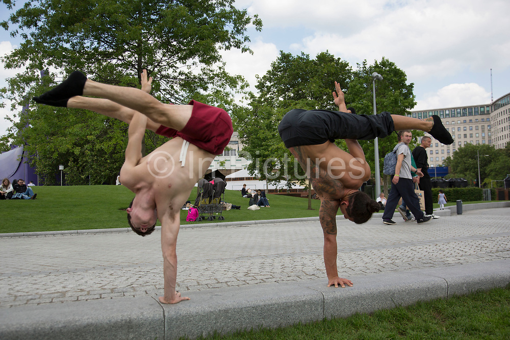 Acrobats from Gravity and Other Myths Circus, (Daniel Liddiard in red shorts, and Miguel Santana in blue) practise their strength hand balancing act in Jubillee Gardens. The South Bank is a significant arts and entertainment district, and home to an endless list of activities for Londoners, visitors and tourists alike.