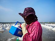 28 MARCH 2018 - BAN LAEM, PHETCHABURI, THAILAND: A worker takes a drink of water during her shift in the salt fields during the 2018 salt harvest in Petchaburi province, about two hours south of Bangkok. Sea salt is made in provinces south of Bangkok by flooding fields with ocean water after the rainy season. As the fields dry out from evaporation, workers go into the fields and gather the salt left behind.  PHOTO BY JACK KURTZ