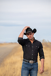 attractive cowboy standing in a field