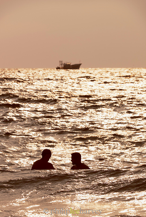 Friends swim in the warm ocean, against the backdrop of a fishing boat at Kovalam Breach, near Trivandrum (Thiruvananthapuram), Kerala, India
