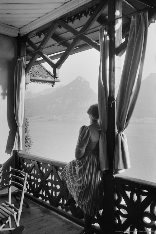 Woman looking out of covered porch, Lake Wolfgang, St. Gilgen, Austria, 1931