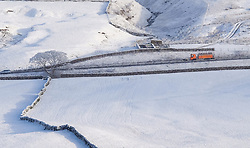 © Licensed to London News Pictures. <br /> 12/12/2014. <br /> <br /> Cumbria, United Kingdom<br /> <br /> A snowplough drives across the A66 in Cumbria as snow lies in fields either side of the road. <br /> <br /> <br /> Photo credit : Ian Forsyth/LNP