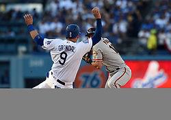 March 29, 2018 - Los Angeles, CA, U.S. - LOS ANGELES, CA - MARCH 29: San Francisco Giants Second base Joe Panik (12) turns to first as Los Angeles Dodgers Catcher Yasmani Grandal (9) slides into second for the out during the MLB opening day game between the San Francisco Giants and the Los Angeles Dodgers on March 29, 2018 at Dodger Stadium in Los Angeles, CA. (Photo by Chris Williams/Icon Sportswire) (Credit Image: © Chris Williams/Icon SMI via ZUMA Press)