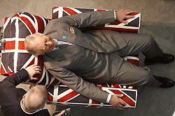 © Licensed to London News Pictures.  16/03/2012. LONDON, UK. Prince Charles (pictured) tries a Sterling Rise and Recline chair in Union Jack fabric at the Ideal Home Show in Earls court London. Made by Adjustamatic the chair retails for £1,950 and is being sold at the show by Sales director Tim Savage (pictured bottom left). The show begins today and runs from the rest of March. Photo credit :  Cliff Hide/LNP