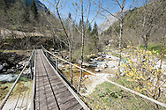Wooden swing bridge over side stream flowing into the River Soca on the Alpe Adria Trail, Triglav national park, Slovenia. The Alpe Adria Trail (AAT) is a 750km hiking route through Austria, Slovenia and Italy. © Rudolf Abraham