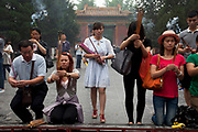 "People come to pray and burn incense sticks at The Yonghe Temple, also known as the ""Palace of Peace and Harmony Lama Temple"", the ""Yonghe Lamasery"", or - popularly - the ""Lama Temple"" is a temple and monastery of the Geluk School of Tibetan Buddhism located in the northeastern part of Beijing, China. It is one of the largest and most important Tibetan Buddhist monasteries in the world. The building and the artworks of the temple is a combination of Han Chinese and Tibetan styles."