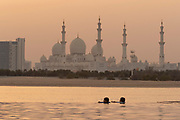 Two boys in the swimming pool at Shangri La Hotel with the view of the Sheikh Zayed Mosque in the background at sunset, Abu Dhabi, United Arab Emirates