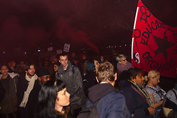 London, November 26th 2014. A vigil for teenager Mike Brown who was shot dead by a policeman in Ferguson, Missouri this year, takes place outside the US embassy in London. Anti-racism and human rights campaigners called the 'emergency' protest following a court verdict that clears Police Officer Darren Wilson of murder. PICTURED: The anti-police-racism protest march begins at the US embassy with smoke flares being ignited.