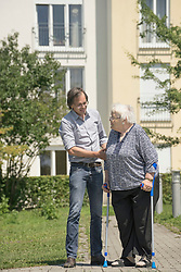 Son walking with disabled mother on crutches, Bavaria, Germany