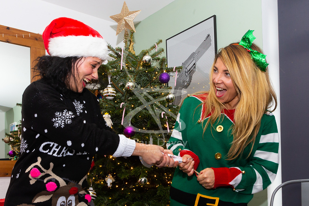Miriam and Barby (R) pull crackers in front of the Christmas tree. Brighton, December 16 2018.