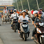 Scooters crossing the bridge Cau Phu Xuan in Hue, Vietnam, in evening rush hour traffic.