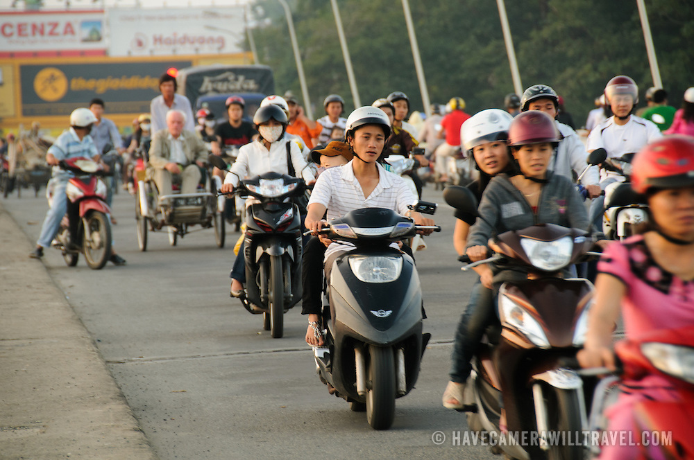Scooters crossing the bridge Cau Phu Xuan in Hue, Vietnam, in evening rush hour traffic.