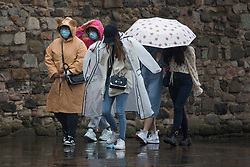 © Licensed to London News Pictures.  09/09/2021. Edinburgh, Scotland. People take shelter from the rain underneath umbrellas in front if the Scottish Parliament in Edinburgh. Scotland is currently the Covid capital of the UK with 17 out of 20 hotspots north of the border. Photo credit: Marcin Nowak/LNP