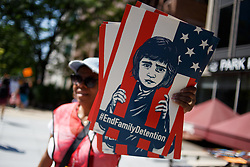 June 30, 2018 - Washington, District of Columbia, USA - A volunteer passes out signs in Lafayette Park, across from the White House, before the Families Belong Together rally. (Credit Image: © Michael Candelori via ZUMA Wire)