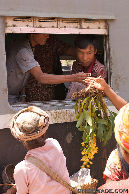 Travelers by goods from vendors on a train near Kalaw, Myanmar.