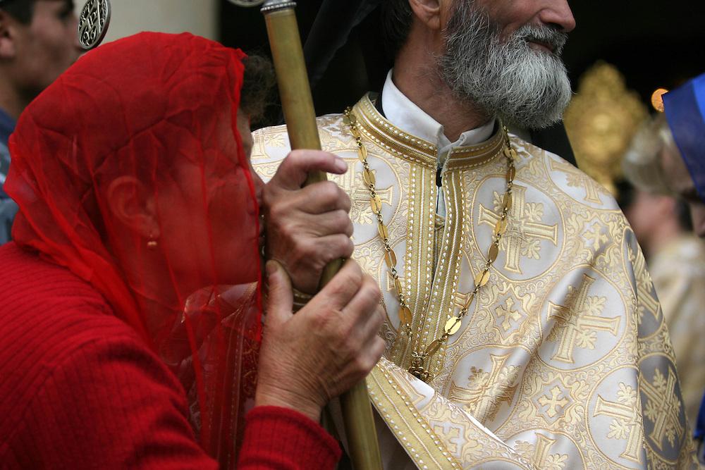 O femeie saruta mana unui preot care oficiaza slujba de Inaltare la Patriarhia din Bucuresti, joi, 1 iunie 2006.