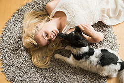 Directly above shot of young woman playing with her dog lying on floor at home, Munich, Bavaria, Germany