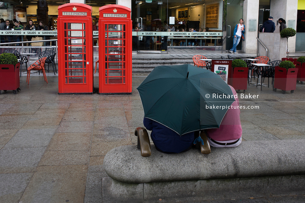 Two anonymous people share a brolley in a pedestrian pavement near London's Trafalgar Square phone boxes.