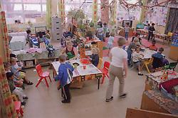 Teachers and nursery school children in classroom,