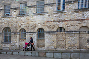 A woman pushed her baby pushchair along a ramp outside Malmaison Boutique Hotel in Oxford Castle Quarter, England, United Kingdom.  The boutique hotel is in a converted prison in a medieval castle in one of the oldest, busiest and trendiest parts of the city.