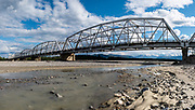"""The Black Veterans Memorial Bridge carries the Alaska Highway across the Gerstle River, 29 miles east of Delta Junction, in Alaska, USA. Free camping is available at Gerstle River Wayside just west of the bridge. Originally built in 1944, it is one of four """"steel through truss-style"""" bridges on the Highway. It was renamed the Black Veterans Memorial Bridge in 1993 as a tribute to 3695 soldiers of the Army and the Corps of Engineers for their contribution in building the Alaska Highway. This image was stitched from multiple overlapping photos."""