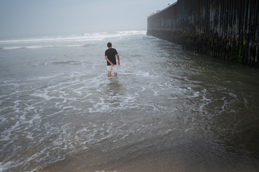Olman Paz, from Progreso, Yoro, Honduras, observes the wall that divides the US and Mexico at the Tijuana border.