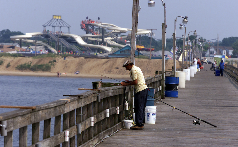 (DAYIN) Keansburg 7/3/2002   A fisherman on the Keansburg fishing pier tries his luck with the view of the water park in the background.      Michael J. Treola Staff Photographer.............MJT