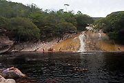 Chapada Diamantina national park in Bahia, Brazil is a very large park conprising miles of trails, several settlements and spectacular scenery. Mosquito swimming hole with people swimming in it.